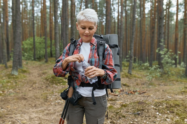 Outdoor shot of active caucasian middle aged woman carrying backpack opening bottle of water, refreshing herself during long exhausting trekking in national park, standing against pine trees