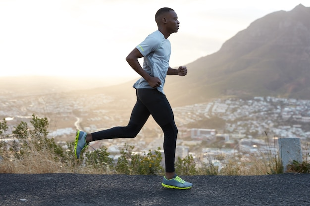 Outdoor shot of active dark skinned man running at morning, has regular trainings, dressed in tracksuit and comfortable sneakers, concentrated into distance, sees finish far away.