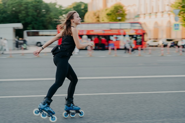 Outdoor shot of active slim young woman enjoys rollerskating during spare time dressed in blackactive wear poses in urban place on road against blurred background with transport. hobby concept
