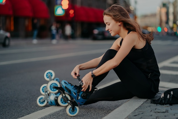 Outdoor shot of active woman laces rollerblades prepares for ride sits on road against busy city background dressed in black activewear enjoys rollerskating. sporty lifestyle and recreation concept