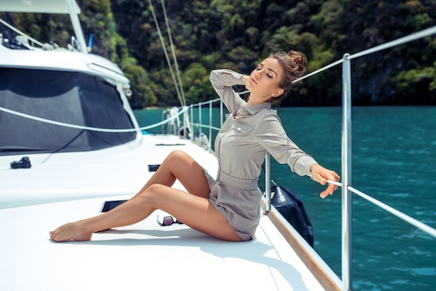 Outdoor shot of adorable young woman in beige dress sitting on edge of yacht