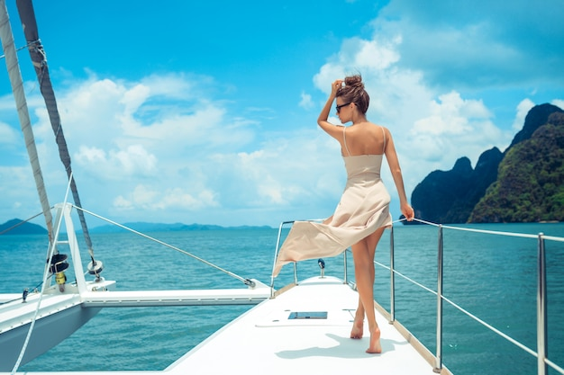 Outdoor shot of adorable young woman in a beige dress standing on edge of yacht, looking to beautiful nature landscape during trip. happy woman enjoying summer travel.