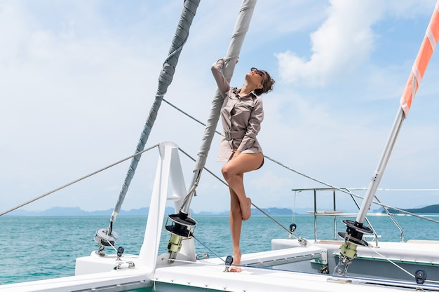 Outdoor shot of adorable young woman in beige dress standing on edge of yacht