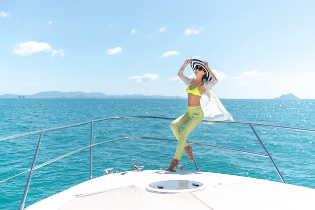 Outdoor shot of adorable young woman in a summer suit and hat sitting on edge of yacht
