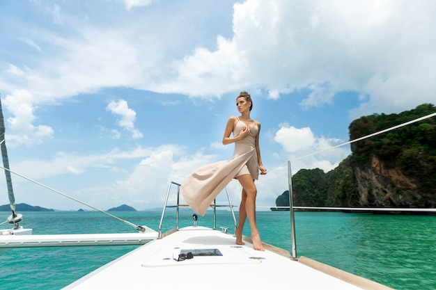 Outdoor shot of adorable young woman in white beige dress standing on edge of yacht