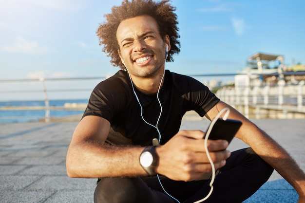 Outdoor shot of afro-american sportsman with bushy hairstyle squinting because of sun in black sport clothing. dark-skinned male athlete sitting cross-legged holding in his hand cell phone