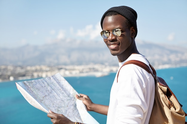 Outdoor shot of atrractive trendy looking dark-skinned tourist studying paper map in his hands, wearing shades and hat, standing on sightseeing platform, contemplating amazing azure sea below