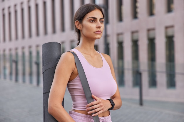 Outdoor shot of attentive young fitness model prepares for pilates exercising carries karemat looks forwards thinks about healthy lifestyle strolls in modern city admires views feels motivated