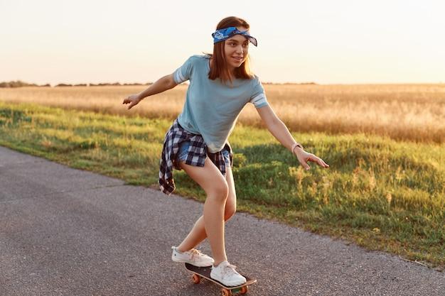 Colpo all'aperto di una donna attraente che indossa abiti in stile casual in sella a skateboard per strada, distogliendo lo sguardo con un sorriso ed esprimendo concentrato, essendo felice del suo successo.