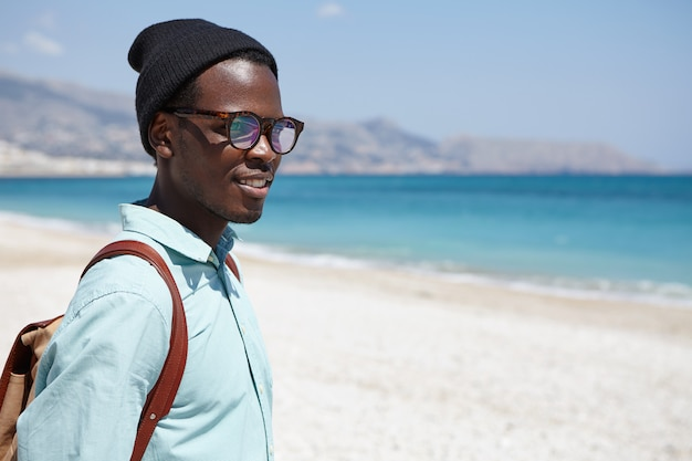 Outdoor shot of attractive happy young african traveler with backpack dressed in stylish clothing relaxing on desert beach early in the morning, contemplating calm sea