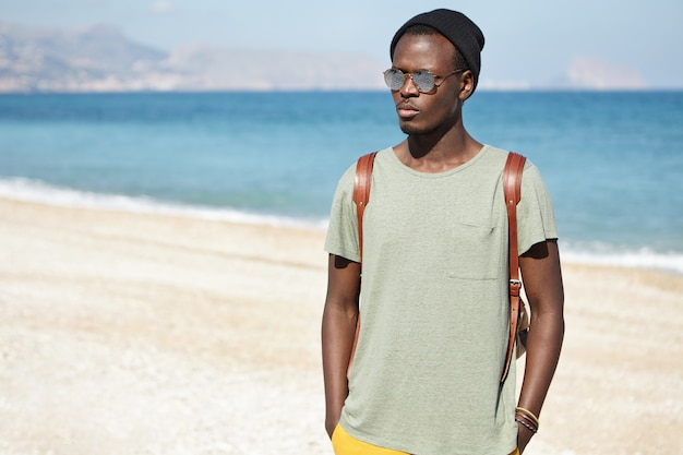 Outdoor shot of attractive serious african male wearing round shades and hat spending vacations by the sea