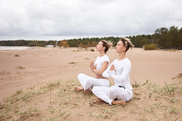 Outdoor shot of attractive young woman and man dressed in similar white clothes sitting barefooted on deserted sandy beach with legs crossed, meditating, keeping eyes closed, making namaste gesture