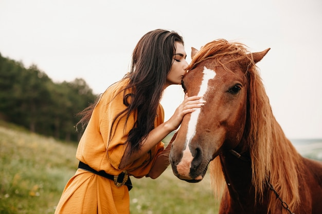 Outdoor shot of a attrative young girl kissing a horse on a filed.