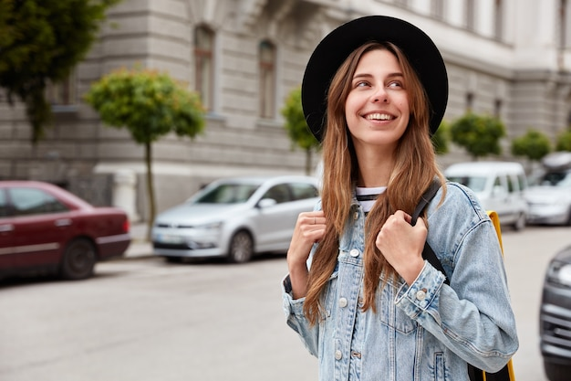 Outdoor shot of beautiful european woman strolls through city, spends free time, recreats during vacation, wears hat and denim jacket