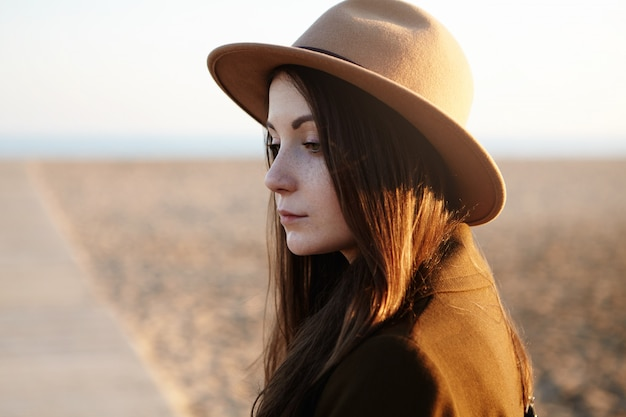 Outdoor shot of beautiful young european woman with long dark hair wearing hat while having walk on city beach, feeling sad and lonely