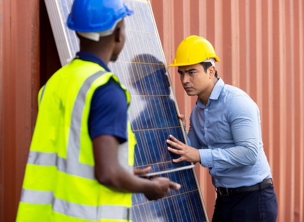 Outdoor shot of black african engineer inspect electrical solar panel wearing hardhat, protective eyeglass and safety equipment,