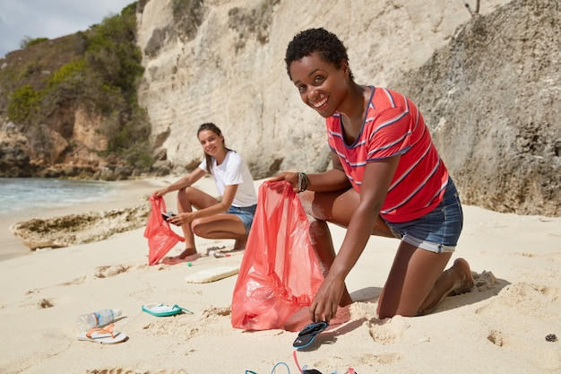 Outdoor shot of black girl dressed casually, collects litter on shore