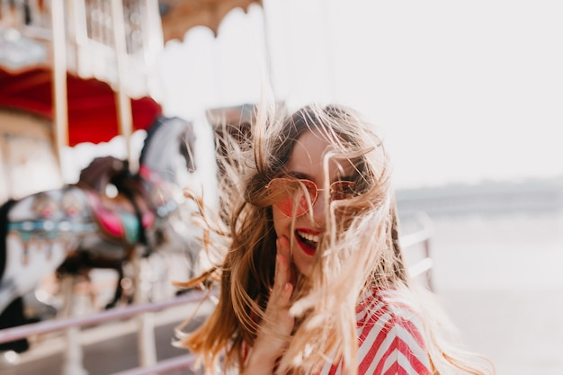 Outdoor shot of blissful cute girl expressing positive emotions. dreamy young woman in sunglasses posing with pleasure in amusement park.