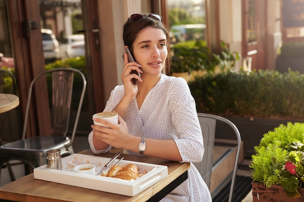 Outdoor shot of charming young dark haired lady in elegant clothes sitting at table on summer terrace and drinking coffe, looking thoughtfully aside while having phone conversation