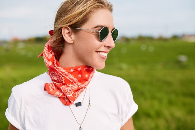 Outdoor shot of cheerful female motorcyclist wears stylish shades and bandana, enjoys freedom as walks across calm green field, admires wonderful nature landscapes.