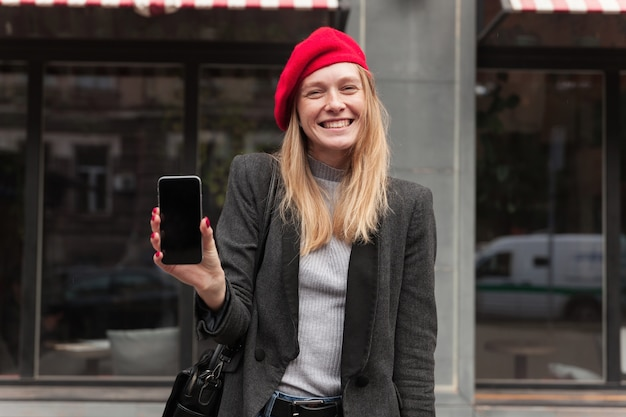 Outdoor shot of cheerful young pretty blonde long haired lady in red beret showing screen of her phone and looking happily with broad smile, standing over cafe exterior