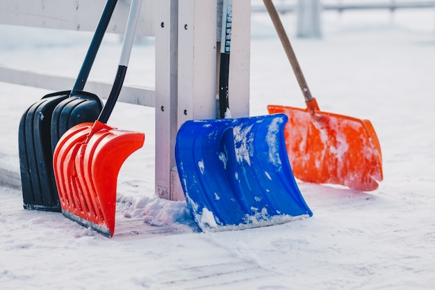 Outdoor shot of colourful shovels against snow background during winter