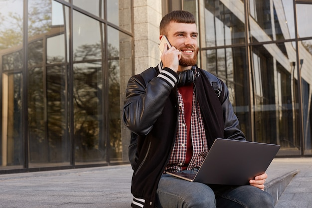 Outdoor shot of cool red bearded young man, sitting on the street putting the laptop on lap, has a telephone conversation with friend, enjoys excellent cellular communication and free wi-fi
