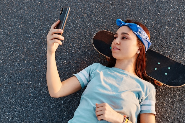Outdoor shot of dark haired beautiful female wearing t shirt and hair band laying down on road in the middle of street, holding smart phone in hands, taking selfie.