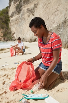 Outdoor shot of dark skinned girl picks up plastic containers, poses on dirty beach