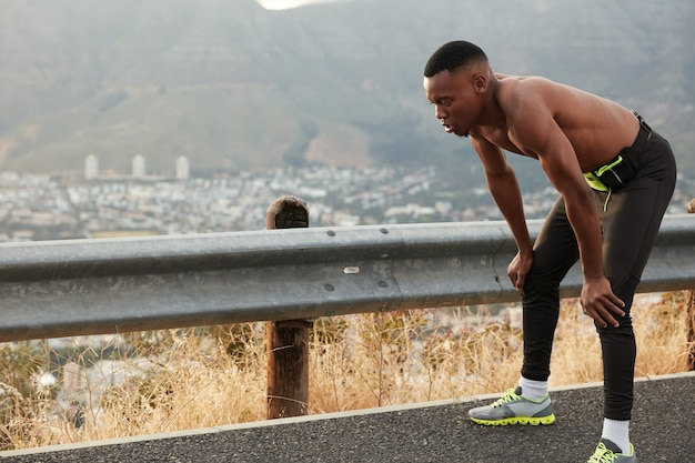 Outdoor shot of dark skinned man leans at knees, has shortness of breath after racing competitions, wears sneakers, has nice endurance, stands over rocky mountain. sport and workout concept