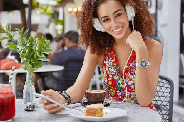 Colpo esterno di felice felice dalla pelle scura giovane femmina indossa camicetta rossa, ascolta la canzone audio in cuffia