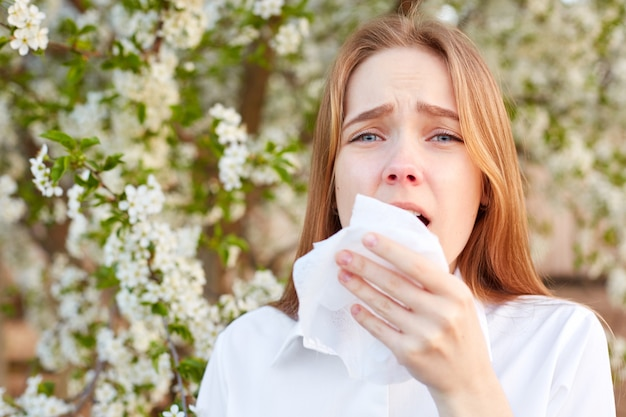 Outdoor shot of discontent young girl has seasonal allergy, uses tissue, poses over blooming tree, has rhinitis and sneezing, reacts on allergens. horizontal view. people and disease concept