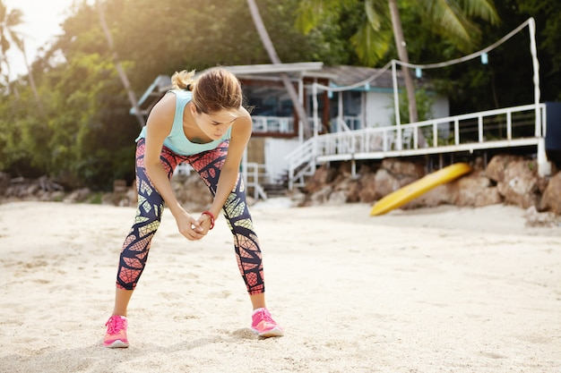Outdoor shot of exhausted caucasian female runner wearing colorful leggings and pink sneakers having rest during intensive workout at the sea, standing on sand and leaning over, catching her breath