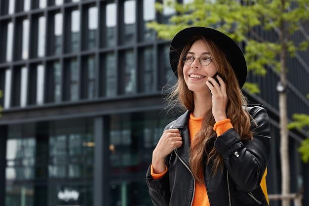 Colpo all'aperto di felice donna europea gode di comunicazione su smart phone, passeggiate nella metropoli, guarda con un ampio sorriso in lontananza