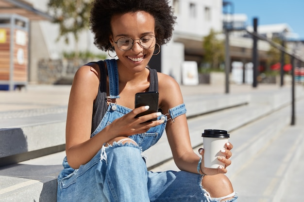 Colpo esterno di hipster felice che legge commenti sul sito web, si concentra sullo schermo del telefono cellulare, tiene un caffè da asporto, si siede sulle scale, indossa abiti in denim, gode di internet ad alta velocità in roaming.