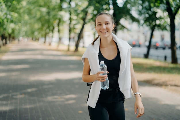 Outdoor shot of glad sporty woman drinks fresh water from bottle has walk during summer green urban park has toothy smile on face leads healthy lifestyle. restoring aqua balanace after training
