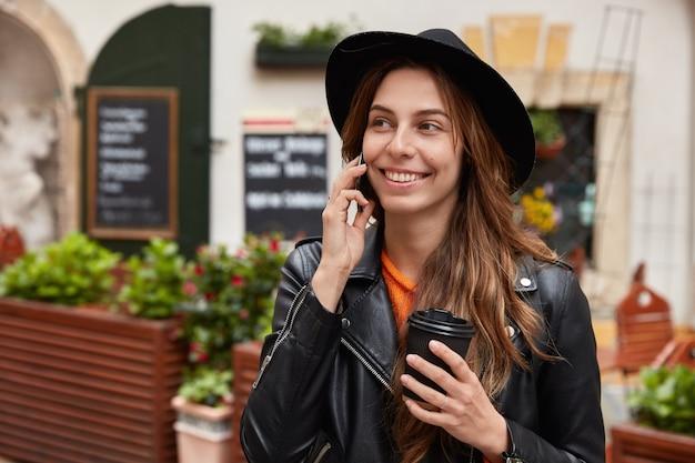 Colpo all'aperto di turista felice ha una conversazione telefonica, posa vicino alla caffetteria con terrazza, tiene il caffè per andare