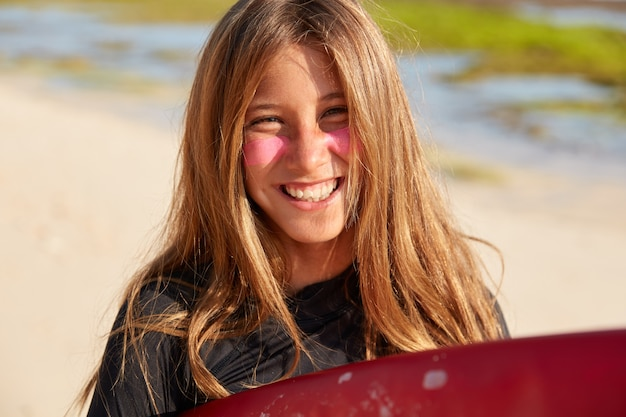 Outdoor shot of good looking smiling woman has pleased expression, applies sick layer of surf zinc on face