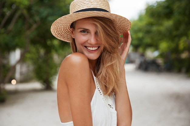 Outdoor shot of good looking young happy female with broad shining smile, wears summer stylish clothing