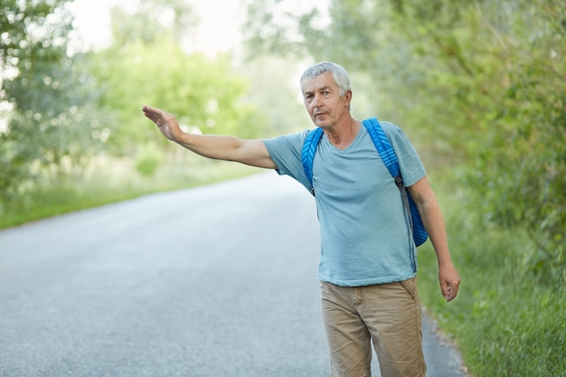 Outdoor shot of grey haired senior man in casual t shirt, has vacation trip, hitchhikes on road in countryside, has rucksack on back. traveling, tourism and hitchhiking concept.