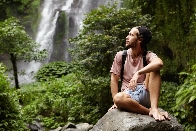 Outdoor shot of handsome barefooted young traveler with beard having rest on big rock during his hiking trip in rainforest