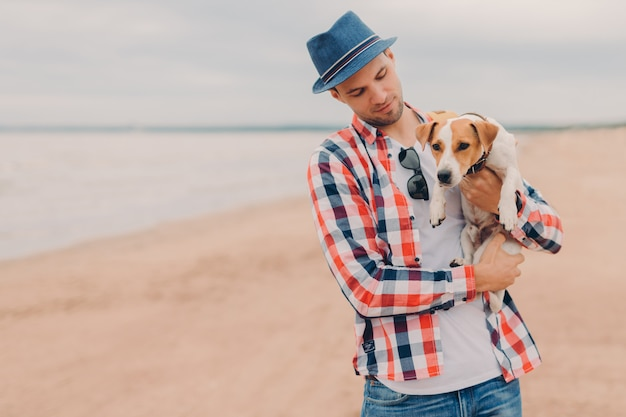 Outdoor shot of handsome man wears hat and checkered shirt, carries favourite dog in hands