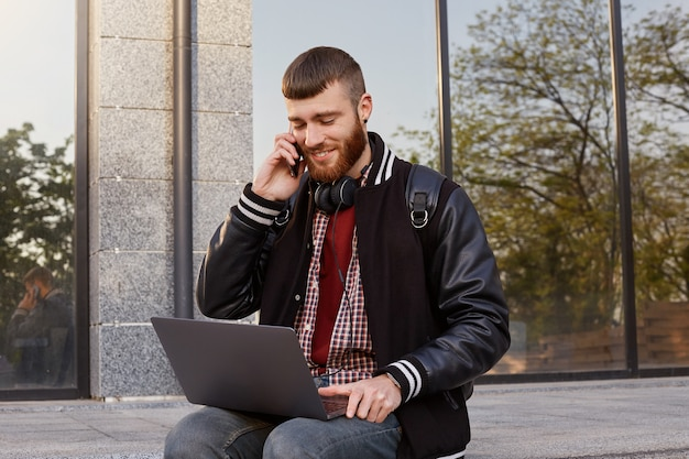 Outdoor shot of handsome red bearded young guy, sitting on the street putting the laptop on lap, smiling, calls his girlfriend and book online movie tickets