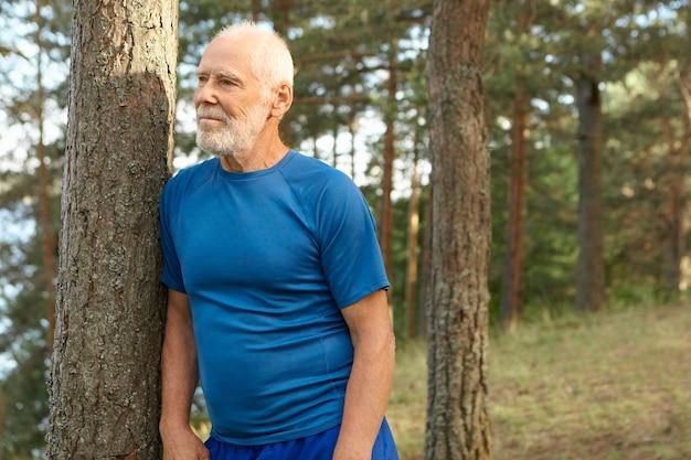 Colpo all'aperto dell'uomo caucasico barbuto anziano bello che indossa la maglietta asciutta blu adatta che posa in legno, spalla pendente sul pino, avendo riposo dopo l'allenamento cardio mattutino, ammirando il bellissimo paesaggio