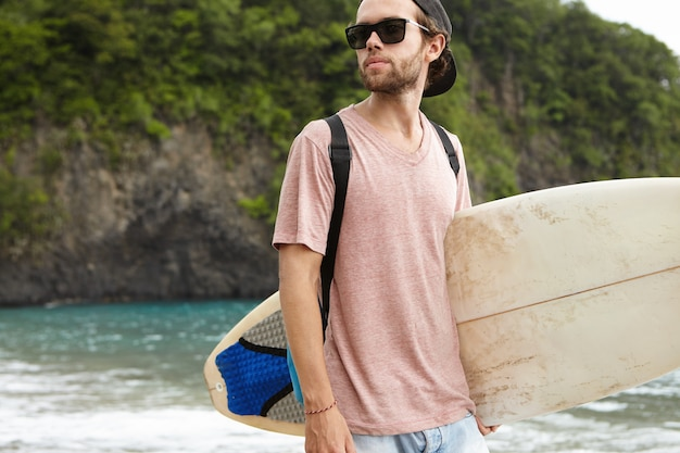 Outdoor shot of handsome young caucasian bearded male model in sunglasses and with backpack posing on beach with rocky shore and looking away with confident expression before surfing training
