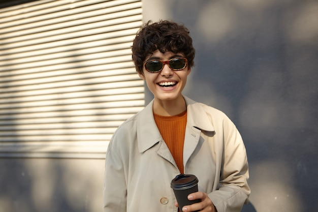 Outdoor shot of happy attractive young curly woman with short dark hair posing on street in city during sunny day, smiling widely and holding paper cup in her hand