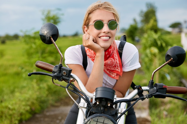 Outdoor shot of happy blonde female motorcyclist wears casual t shirt and sunglasses, look into distance with cheerful expression, sits on motorbike, poses in countryside. traveling and freedom