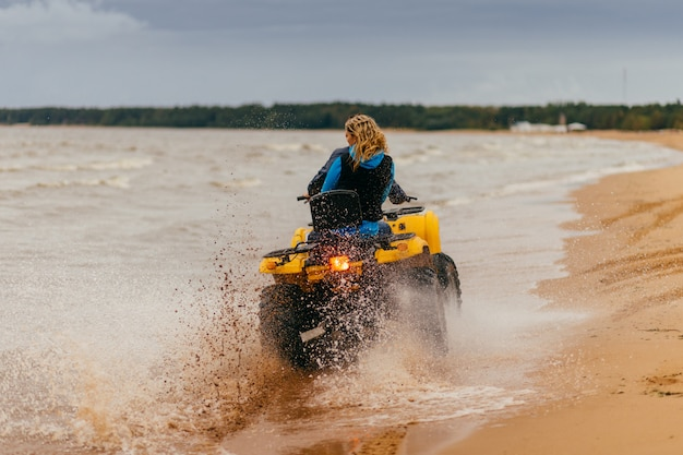 Outdoor shot of happy couple ride quadrocycle on seashore