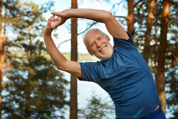 Outdoor shot of happy energetic senior retired man enjoying physical training in park, doing side bends exercise, holding hands together with broad smile, warming up body before run
