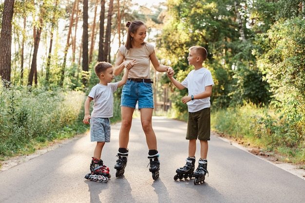 Outdoor shot of happy family having fun and roller skating together in summer park, mommy holding kids hands, being glad to spend weekend together, active pastime.